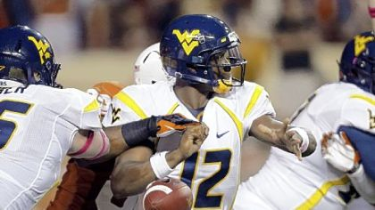 West Virginia's Stedman Bailey (3) leaps for a touchdown pass as Texas' Carrington Byndom (23) defends in the third quarter Saturday night in Austin, Texas.