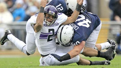 Northwestern quarterback Kain Colter is tackled by Penn State cornerback Stephon Morris and linebacker Glenn Carson during the second quarter at State College.