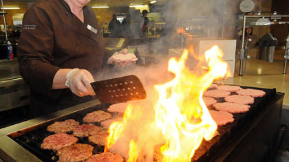 Shelby Lehman makes made-to-order burgers on the grill at Shippensburg University's Reisner Dining Hall.