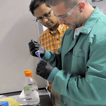 Duquesne University professor Partha Basu, left, who has studied arsenic contamination in food, observes grad student John Thomas prepare compounds to be analyzed.