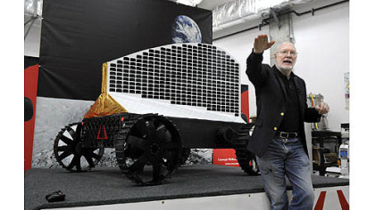 "William ""Red"" Whittaker, CEO of Astrobotic Technology Inc. and founder of the Field Robotics Center at Carnegie Mellon University's Robotics Institute, talks about Polaris, displayed behind him. The solar-powered robot will search for deposits of ice at the moon's poles."