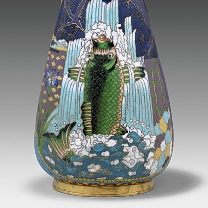 The strong influence of Japanese designs is seen in this vase created in 1875 by Elkington & Co. Made of enamel and gilded brass, it shows a carp against a waterfall framed by pine branches.