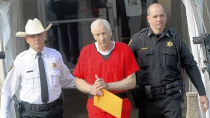 Jerry Sandusky in escorted from the Centre County Courthouse after sentencing. Centre County Sheriff Denny Nau is at left.