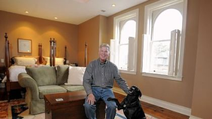 Ty Ely and his dog Bobbie in the master bedroom on the third floor of the Elys' Shadyside home. The king-size bed is made from twin beds Tye's wife Sue inherited from her grandfather.