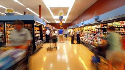 Shoppers check the offerings in a Giant Eagle dairy aisle. The grocer is locking prices on some staples at a time of rising commodity prices.