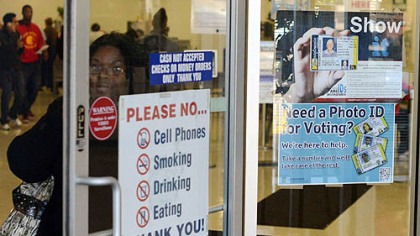 A woman walks past a voter identification poster today at the PennDOT drivers' license center in Penn Hills.