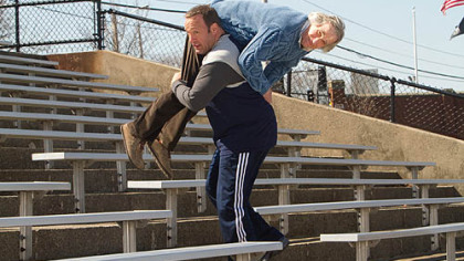 "As Scott Voss, Kevin James carries Henry Winkler, who portrays a fellow teacher, over his shoulder as added weight while he works out for mixed martial arts fighting in ""Here Comes the Boom."""