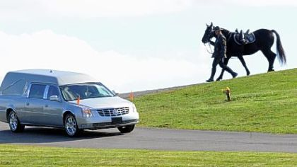 A Trooper leads a horse following the hearse carrying Trooper First Class Blake T. Coble to the graveside ceremony held at St. Mary's Roman Catholic Church Cemetery in Beaver Falls.