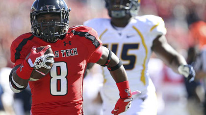 Texas Tech's SaDale Foster breaks free for a touchdown ahead of West Virginia's Eric Kinsey.