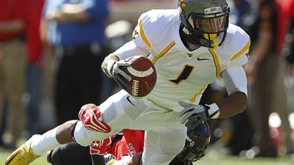 West Virginia's Tavon Austin is tackled by Texas Tech's D.J. Johnson.