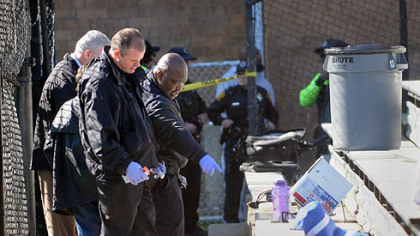 Pittsburgh police investigators look over the scene of a shooting at a peewee football game this morning adjacent to the Pittsburgh Obama International Studies Academy in East Liberty.