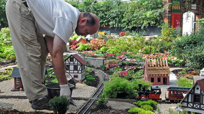 Kevin Ajughey spreads ballast along the train tracks in the Garden Railroad as the finishing touches are done for the fallshow at Phipps Conservatory.
