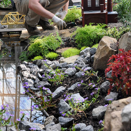 Matt Urian fills in small scenic details in the Garden Railroad at Phipps Conservatory.