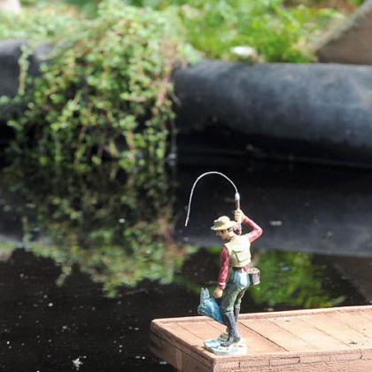 A fisherman casts a line into the pond near the model railroad in Phipps Conservatory.