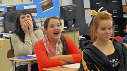 "Sitting behind eighth-grade students Julia Horvitz and Mikayla Horick, both 13, in a social studies class, science teacher Christina Becker reacts to a student's attempt at reading the news like a ""town crier."""