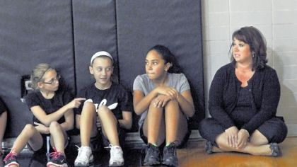 Melissa Gambino, right, a science teacher at Pleasant Hills Middle School, sits Wednesday with sixth-grade students in gym class == from left, Kaley Kuzma, Morgan Newton and Sierra Henning, all 11.
