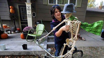 Paige Kaske threads a wire through the ribcage of a skeleton to create the effect of a scarf blowing while decorating her yard this week for Halloween in Sioux Falls, S.D.