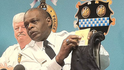 Pittsburgh Police Chief Nate Harper holds up the bullet-resistant vest worn by Officer Andrew Baker, right, to show the bullet hole in the center-chest area.