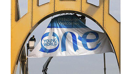 A crew installed a banner Oct. 5 on the Roberto Clemente Bridge for the One Young World Summit.