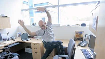 Ron DeAngelo, director of sports performance training at UPMC's Center for Sports Medicine, shows a hip flexing exercise you can do at your desk.