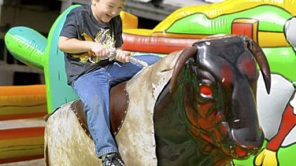 Garett Kime, 6, of Clarksville tries to hold on as he rides the mechanical bull Sunday at the 2012 Roughneck Fest at the Washington County Fairgrounds.