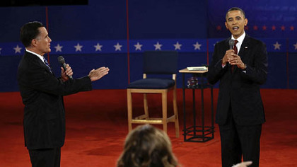 Republican presidential nominee Mitt Romney and and President Barack Obama answer a question during the second presidential debate at Hofstra University tonight.