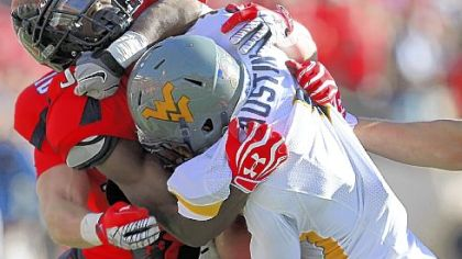 West Virginia's Tavon Austin is taken down by Texas Tech's Cody Davis Saturday in Lubbock, Texas.