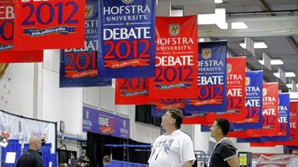 Billy Koske, left, and Jose Reyes look at signs hanging Monday in the media center before tonight's presidential debate at Hofstra University in Hempstead, N.Y.