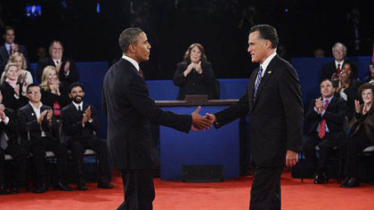 Moderator Candy Crowley, center, applauds as President Barack Obama shakes hands with Republican presidential nominee Mitt Romney during the second presidential debate at Hofstra University.