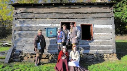 Re-enactors portraying people who lived during the Revolutionary War period are, seated in front, Jessica Baker, left, and Kate Cunning. Standing behind them are, from left, John Cunning, Nathan Baker, Rich Baker and Bryan Cunning. The group is outside of the Bloody Dirt Tavern at the Enoch Wright House in Peters. Bryan Cunning is known for his portrayal of George Washington.