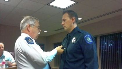 Collier police officer Daniel Elway, right, receiving an award from Chief Tom Devin.