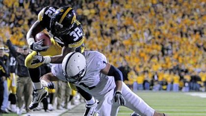 Iowa running back Adam Robinson, left, leaps over Penn State safety Nick Sukay in 2010. Iowa won, 24-3, and the Hawkeyes have won every home game against the Nittany Lions since '01.