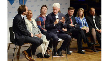 Bill Clinton answers questions while seated with David Jones, the co-founder of One Young World, during the opening ceremony for the One Young World Summit at Heinz Hall.