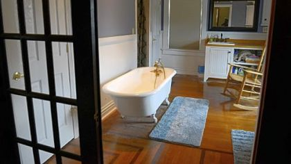 The master bathroom, a former bedroom, has a French door between the bedroom and bath, a double-bowl sink, and a clawfoot tub.
