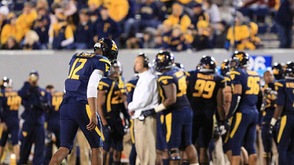 West Virginia quarterback Geno Smith walks off the field after a turnover on downs.