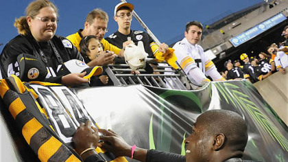 The Steelers' Antonio Brown signs a throwback jersey for a fan during pregame in Cincinnati.