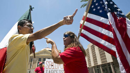 Andy Hernandez, left, carrying a Mexican flag, and Allison Culver, carrying an American flag, continue the discussion over Arizona's immigration law outside the State Capitol in Phoenix.