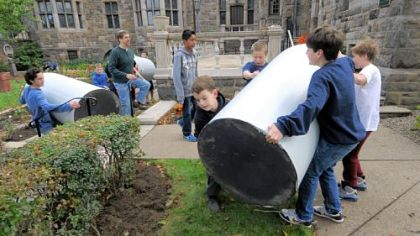 Sixth-graders move rain barrels at Temple Sinai&#039;s rainwater garden in Squirrel Hill.