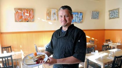 Lola Bistro owner and chef Michael Barnhouse holds a plate of artisan cheeses and house charcuterie.