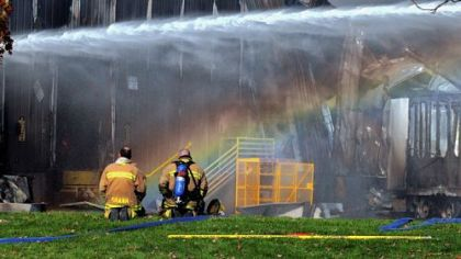A rainbow appears while water is poured on the hotspots of the fire yesterday at a Creps United Publications facility near Indiana, Pa.