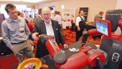 Rethink Robotics product manager Mike Bugda, right, demonstrates the Baxter user-programmable robot.
