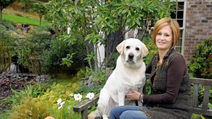 Rose Romboski and her yellow lab, Ashton, in her garden.