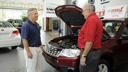 "Harry ""Good News"" Gosnell, a salesman with Cochran Subaru in Monroeville, talks with customer David Goldblum of Connellsville."