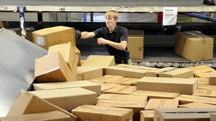 Ryan Craig, a load coach with Fed-Ex, sorts boxes at the Neville Isalnd facility.