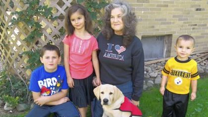 Rebecca Rodock of Penn Township is raising Remi to become a service dog. With them, from left, are her grandson, Chad Beckett, and great-grandchildren Kaylee and Silas Beckett.