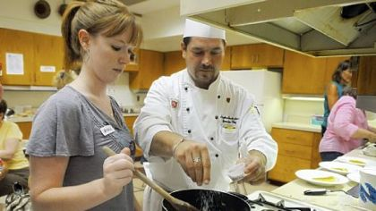 Amanda Petrovich of Fox Chapel helps Stephen J. Grottenthaler, executive chef of Pittsburgh Field Club, in a cooking class at Fox Chapel Area High School.