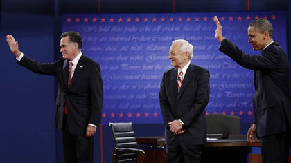 Moderator Bob Schieffer, center, watches as Republican presidential nominee Mitt Romney, left and President Barack Obama  wave to members of the audience during the third presidential debate at Lynn University, Monday, Oct. 22, 2012, in Boca Raton, Fla.