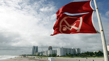 Red flags fly from a lifeguard station as Hurricane Sandy passes east of Miami Beach today. Sandy could blend with a winter storm and reach the East Coast as a super-storm next week.