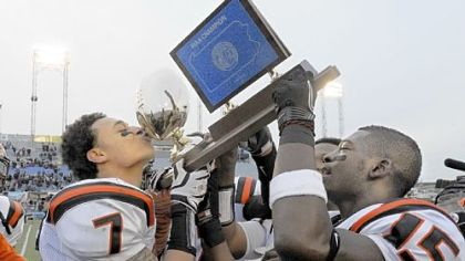 Clairton's Dakota Halcomb kisses the PIAA Class A trophy in 2011. The Bears are riding a 55-game winning streak.