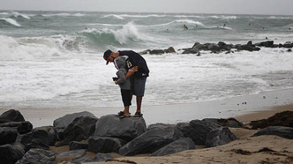 A man and his son watch the rough surf at the inlet in Boynton Beach, Fla., from Hurricane Sandy. Even if the storm doesn't come to Pittsburgh, the weather here will still take a downturn this weekend.